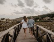 Mallorca elopement wedding photographer photographs couple running away on wooden planks in Cala Mesquida
