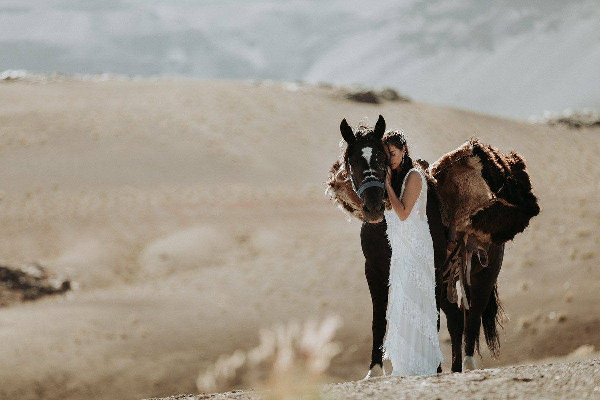 Adventure Wedding photographer - bride with horse in desert during destination wedding in south america